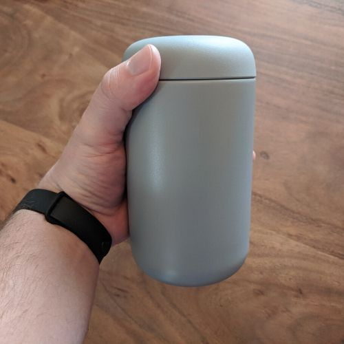 Coffee mug with lid and held in hand